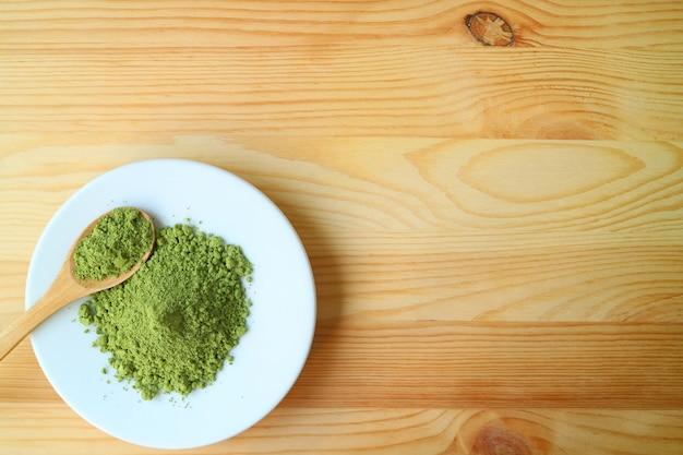 Vista superior de un plato de polvo de té verde matcha con una cuchara de té de madera en mesa de madera
