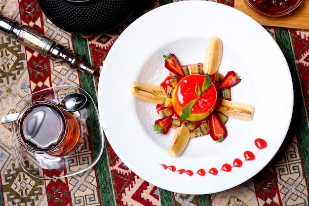 Vista superior del plato de postre adornado con jarabe de fresa plátano kiwi y rodajas de fresa