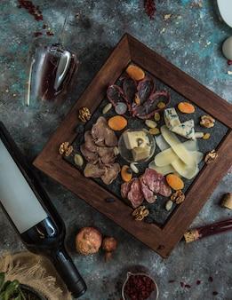 Vista superior del plato de queso con nueces y frutas secas