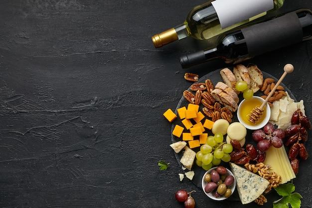 Vista superior del plato de queso sabroso y botellas de vino con fruta, uva, nueces y miel en el escritorio negro.