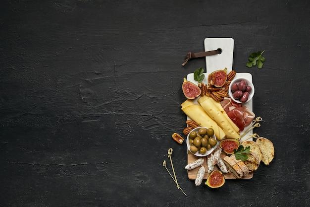 Vista superior del plato de queso sabroso con fruta, uva, nueces, aceitunas y pan tostado en un plato de cocina de madera sobre el fondo de piedra negra, vista superior, espacio de copia. comida y bebida gourmet.