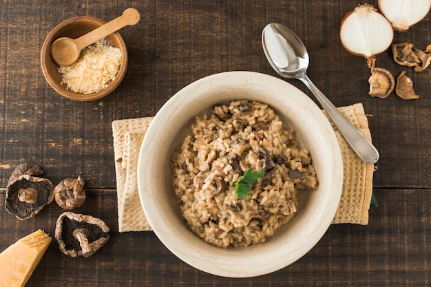 Vista superior del plato de risotto de hongos con ingredientes en mesa de madera