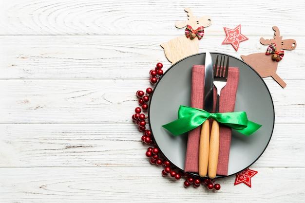 Vista superior del plato, tenedor y cuchillo servido en navidad decorado de madera.