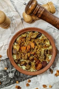 Vista superior de un plato tradicional azerbaiyano pilaf con carne y frutos secos fritos con cebolla en un plato de arcilla en un periódico