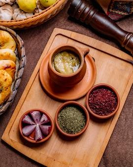 Vista superior de un plato tradicional azerbaiyano piti en una olla con hierbas secas de zumaque y cebollas en una bandeja