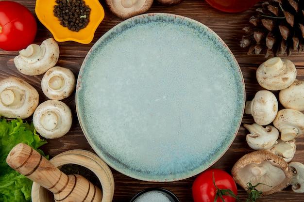 Vista superior de un plato vacío y champiñones frescos con granos de pimienta negra, tomates frescos, mortero de madera con hierbas secas, sal y conos en la mesa de madera rústica