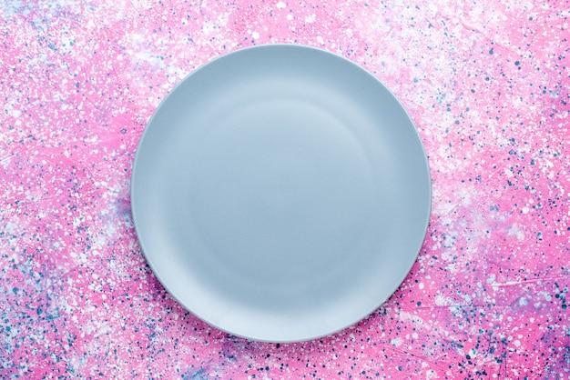 Vista superior del plato vacío de color azul en la pared de color rosa plato de fotos en color comida