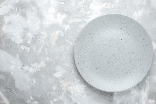 Vista superior del plato vacío gris redondo formado en luz, plato de cocina
