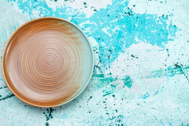 Vista superior del plato vacío marrón aislado en azul, cubiertos de placa