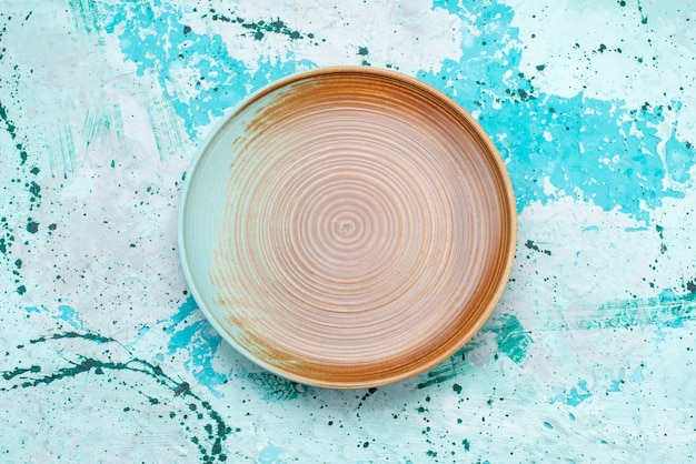 Vista superior del plato vacío marrón en azul claro, plato de comida