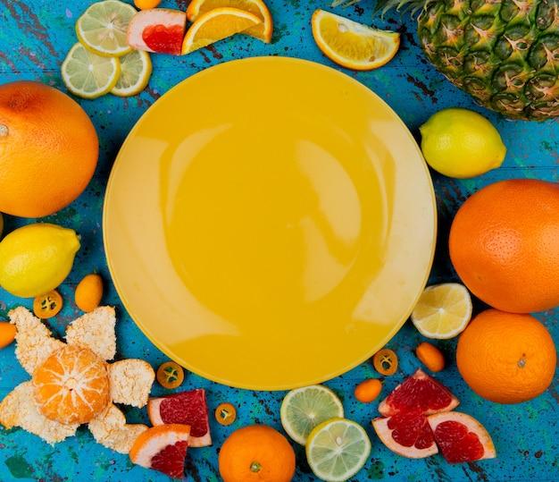 Vista superior del plato vacío con pomelo mandarina limón piña kumquat alrededor sobre fondo azul.