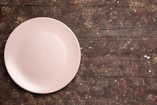 Vista superior del plato vacío rosado en marrón rústico, escritorio de madera, cubiertos de comida