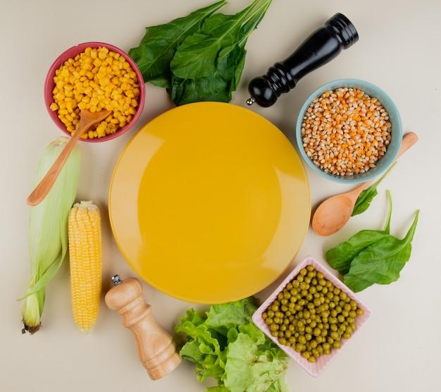 Vista superior del plato vacío con semillas de maíz cocidas y secas, mazorca de maíz con cáscara, lechuga, espinacas, guisantes verdes y cuchara de madera alrededor en blanco
