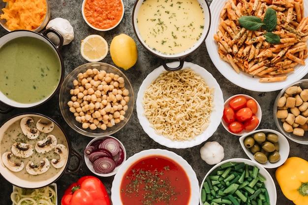 Vista superior de platos con fideos y sopa de tomate