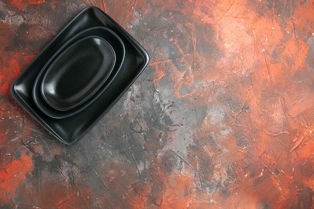 Vista superior de platos ovalados y rectangulares negros sobre una superficie de color rojo oscuro
