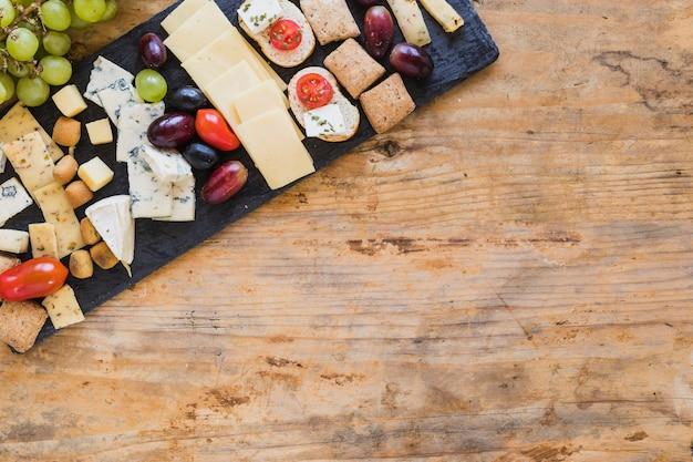 Vista superior de platos de queso con uvas y tomates en mesa