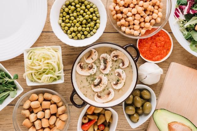 Vista superior de platos con sopa de champiñones y aceitunas