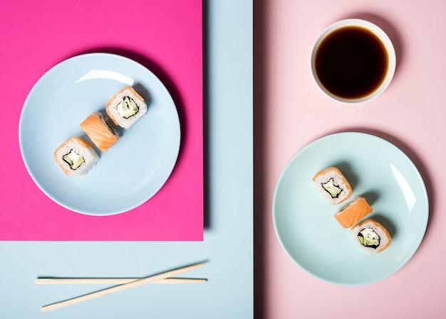 Vista superior de platos de sushi con palillos y salsa de soja