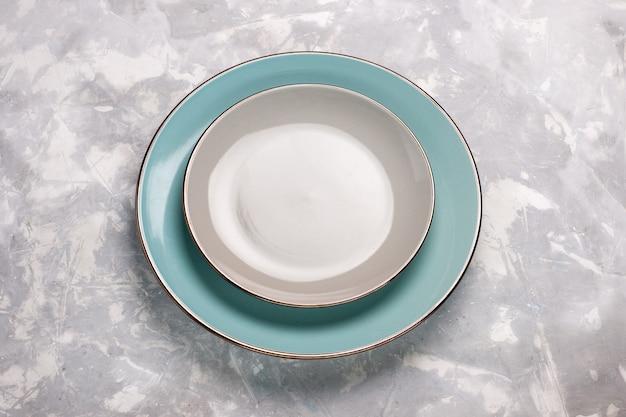 Vista superior de platos vacíos hechos de vidrio sobre una superficie blanca clara
