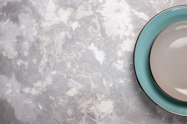 Vista superior de platos vacíos de vidrio sobre escritorio blanco