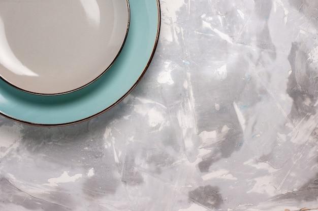 Vista superior de platos vacíos de vidrio sobre superficie blanca