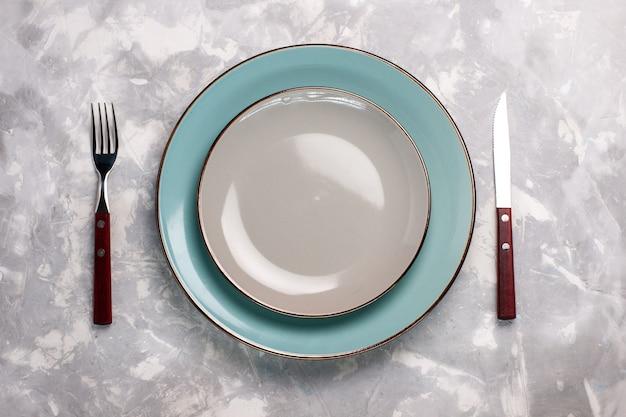 Vista superior de platos vacíos de vidrio con tenedor y cuchillo sobre superficie blanca