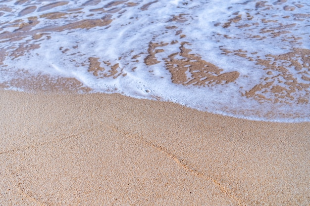 Vista superior de la playa de arena y agua limpia y arena blanca en verano con fondo de cielo azul claro y bokeh de sol.