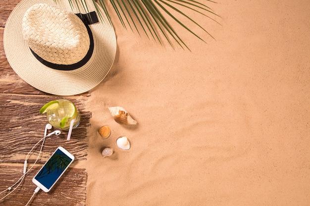 Vista superior de la playa de arena con marco de toalla y accesorios de verano. fondo con espacio de copia y textura de arena visible. borde derecho hecho de toalla