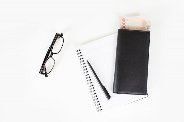 La vista superior de la pluma y el dinero en una bolsa de cuero negro colocada en un libro con anteojos sobre una mesa blanca. con copia espacio.