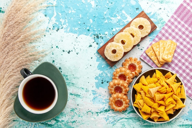 Vista superior poco picantes chips con galletas de piña seca anillos y galletas en el fondo azul chips snack color calorías crujientes