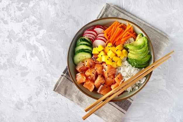 Vista superior del poke bowl con verduras, arroz y salmón.