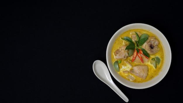 Vista superior de pollo al curry verde tailandés sobre fondo de escritorio negro