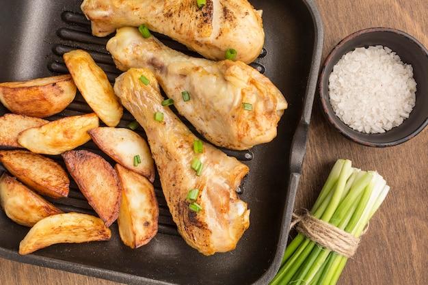 Vista superior de pollo al horno y gajos en sartén con sal y cebollas verdes
