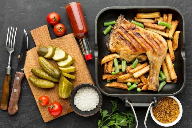 Vista superior de pollo al horno y patatas en sartén con encurtidos y tomates