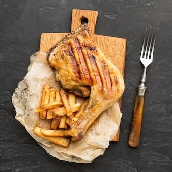 Vista superior de pollo al horno y patatas en tabla de cortar con tenedor