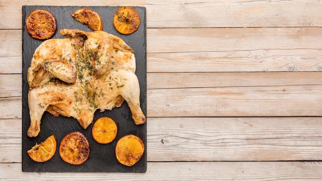 Vista superior de pollo al horno con rodajas de naranja y espacio de copia