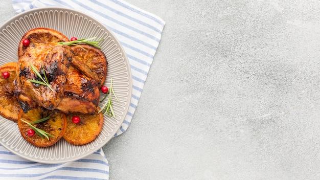 Vista superior de pollo al horno y rodajas de naranja en un plato con un paño de cocina y espacio de copia