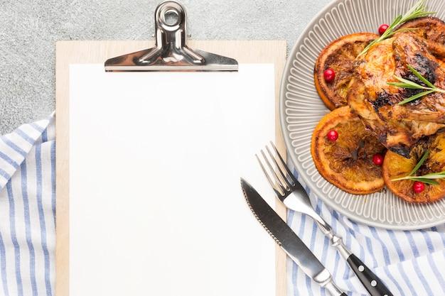 Vista superior de pollo al horno y rodajas de naranja en un plato con papel de cocina y portapapeles en blanco