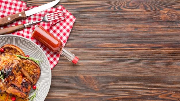 Vista superior de pollo al horno y rodajas de naranja en un plato con salsa y espacio de copia