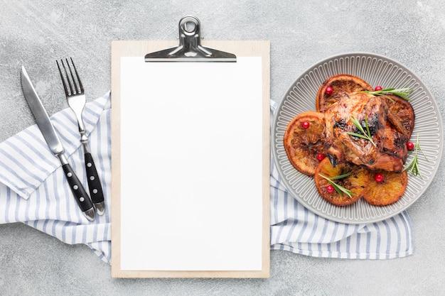 Vista superior de pollo al horno y rodajas de naranja en un plato con una toalla de cocina y un bloc de notas en blanco