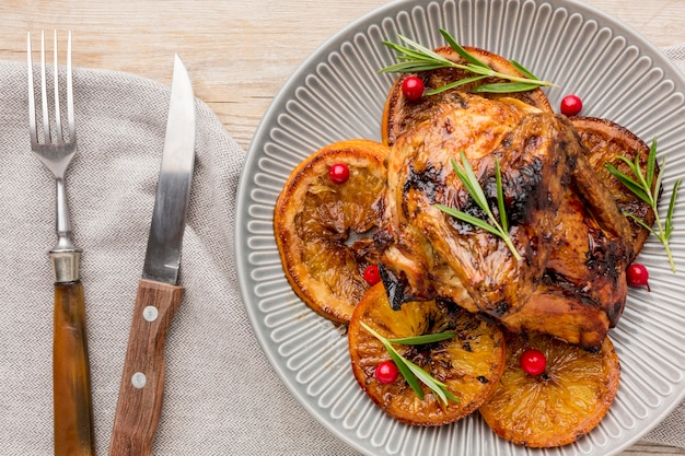 Vista superior de pollo al horno y rodajas de naranja en un plato