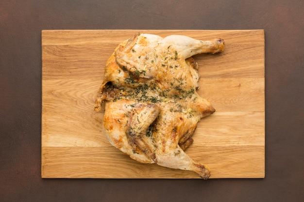 Vista superior de pollo al horno en tabla de cortar