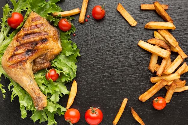 Vista superior de pollo al horno y tomates cherry con papas fritas