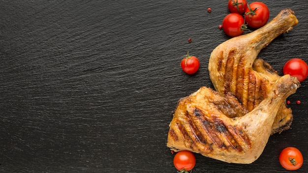 Vista superior de pollo al horno y tomates con espacio de copia