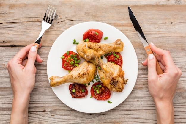 Vista superior de pollo al horno y tomates en un plato con las manos sosteniendo un tenedor y un cuchillo