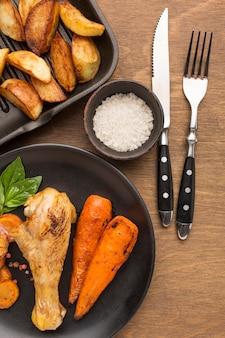 Vista superior de pollo al horno y verduras en un plato con gajos y sal