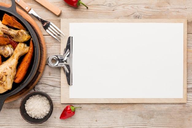 Vista superior de pollo al horno y verduras en una sartén con bloc de notas en blanco