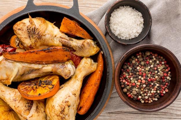 Vista superior de pollo al horno y verduras en sartén con condimentos