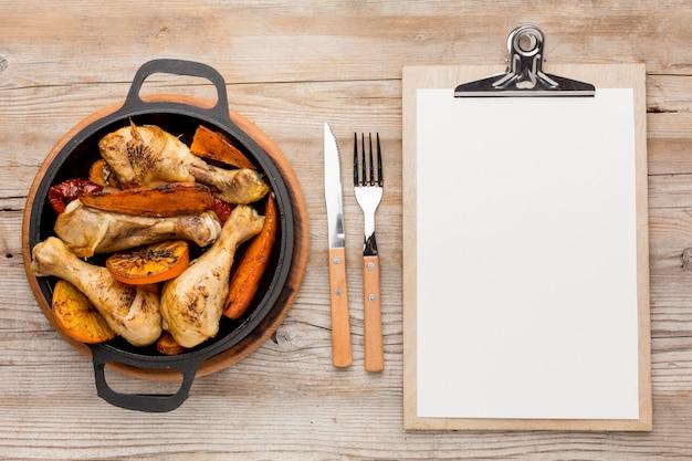 Vista superior de pollo al horno y verduras en una sartén con cubiertos y bloc de notas en blanco
