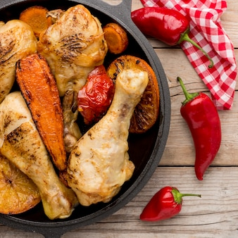 Vista superior de pollo al horno y verduras en una sartén con pimientos rojos